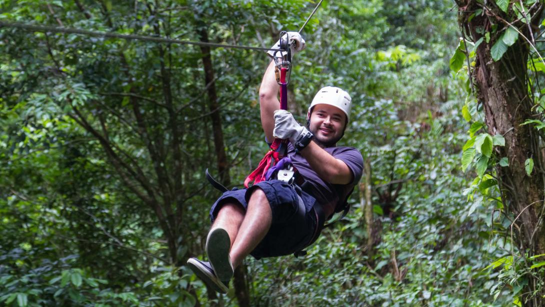 Voyageur fait de la tyrolienne à travers la forêt du Costa Rica.